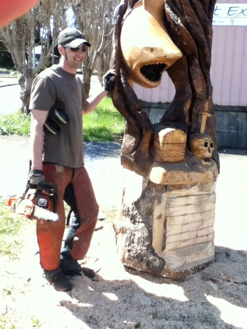 Brian Vorwaller of Artist Extreme, poses in front of his shark carving.  It was all carved from one chunk of wood.