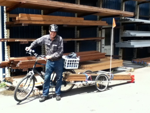 Lumber loaded on bicycle trailer, barely clears ground.