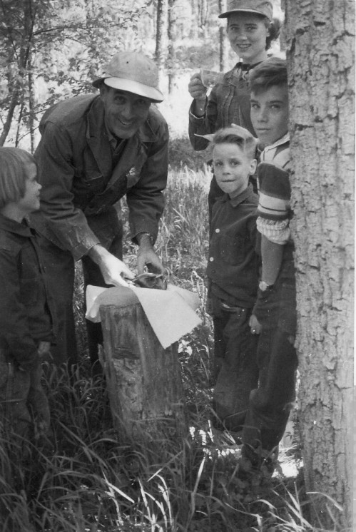 Dad with some of his kids in 1956.  I think he had just caught a fish and was preparing to clean it.  I'm the one leaning against the tree.