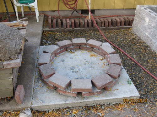 Here I am building a ring of re-purposed paver stones on top of the concrete foundation I poured.  The ring will hold a bunch of rubble (old bits of concrete from pulling old fence posts, broken cinder blocks, rocks etc) that will make a solid base for the oven.