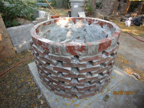 I added on last ring of bricks to raise the height of the oven base a little.  In this case I used standard red clay bricks and set them on edge.  This will let me have a little more insulation between the oven and the base.