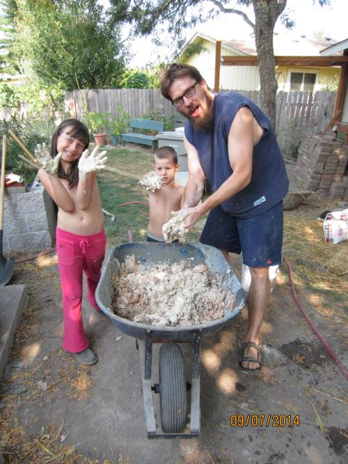 The kids and I mixing up our first batch of 'insulation' for the oven.  We are using a thick clay slip made from fire clay and mixing in pine shavings (livestock bedding).  The idea is when it dries and then gets really hot the wood will undergo pyrolysis (decompose to gaseous products without actual combustion) and leave a sort of clay sponge that should make a good insulator.