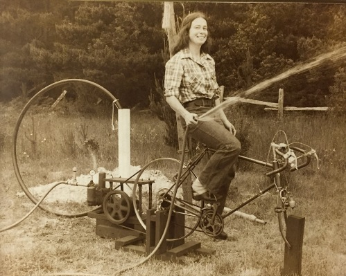 This was probably about 40 years ago, my sweetheart is showing how my bicycle can pump water.  We had bought an old (very old) Fairbanks-Morse water pump and I think we were testing it out.